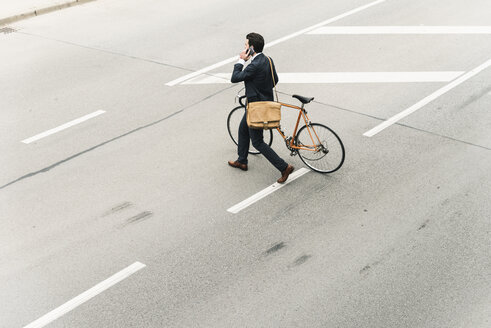 Businessman with bicycle on cell phone walking on the street - UUF14094