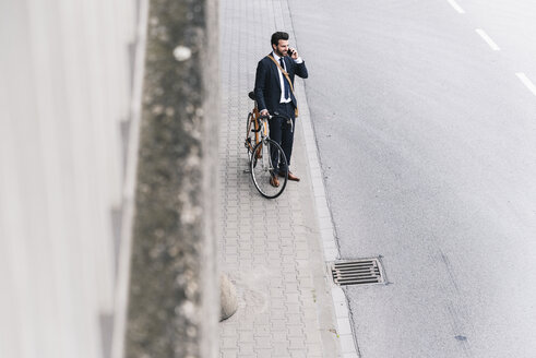 Businessman with bicycle on cell phone at the street - UUF14097