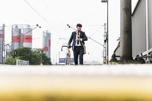Businessman with bicycle waiting at the platform - UUF14100