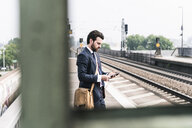 Businessman with cell phone and earphones waiting at the platform - UUF14103