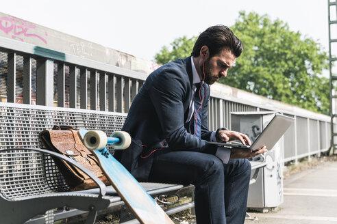 Businessman with skateboard using laptop at the platform - UUF14115