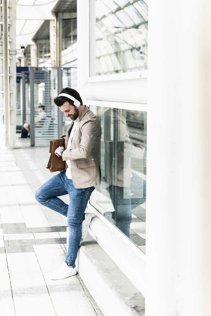 Young man wearing headphones waiting at the station platform - UUF14130 - Uwe Umstätter/Westend61