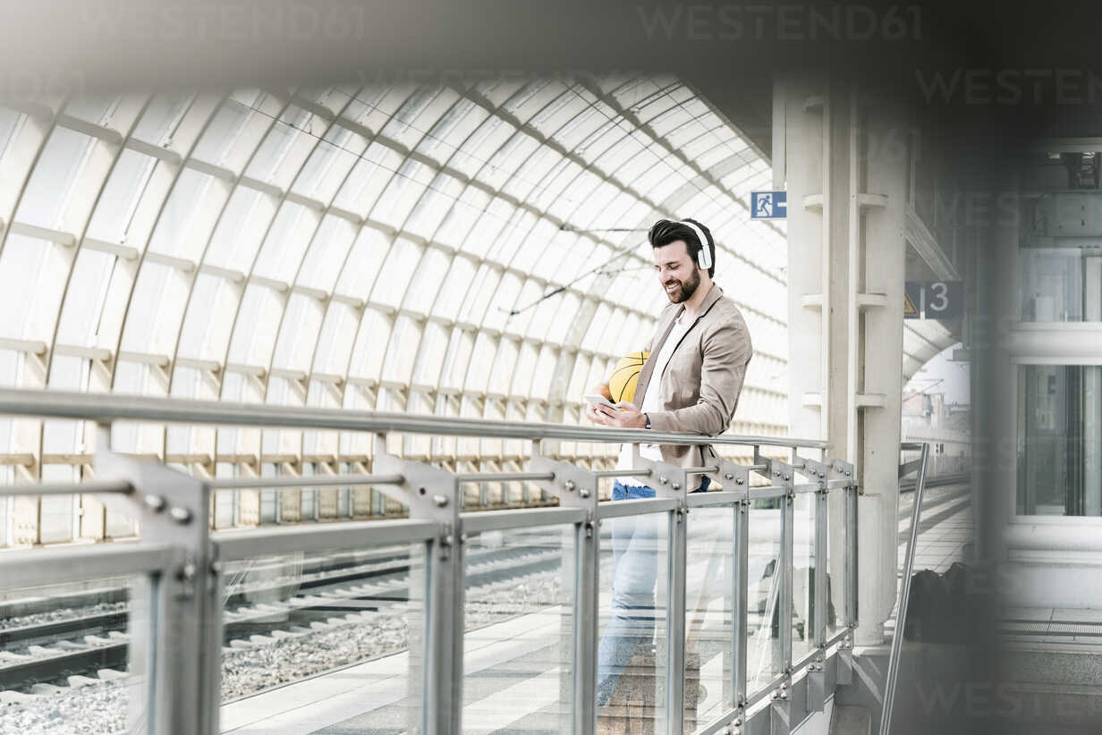Smiling young man with headphones, cell phone and basketball at the station platform - UUF14136 - Uwe Umstätter/Westend61