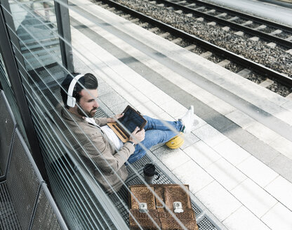 Young man with basketball using tablet at the station platform - UUF14142