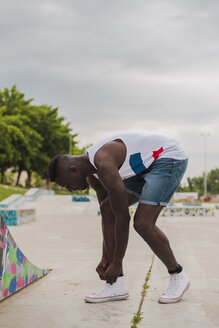 Young man in skatepark, tying shoes - ACPF00001