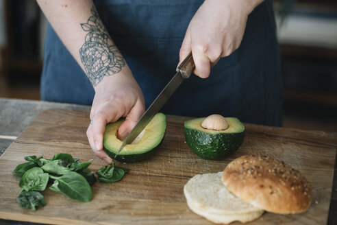 Woman preparing vegan burger, slicing avocado - ALBF00391