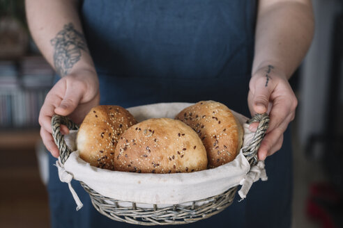 Woman holding basket with homemade vegan bread rolls - ALBF00400