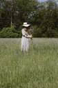 Italy, Veneto, Young woman plucking flowers and herbs in field - ALBF00403