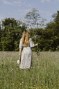 Italy, Veneto, Young woman plucking flowers and herbs in field - ALBF00406