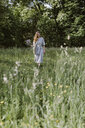 Italy, Veneto, Young woman plucking flowers and herbs in field - ALBF00412