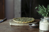 Homemade chickpea and herb cake on wooden table - ALBF00421
