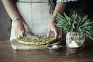 Young woman slicing homemade chickpea and herb cake - ALBF00424