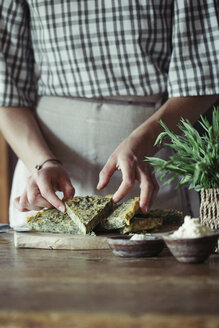 Young woman garnishing homemade chickpea and herb cake - ALBF00430