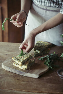 Young woman garnishing homemade chickpea and herb cake - ALBF00436