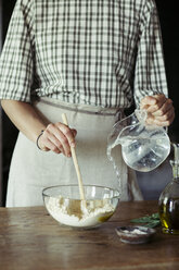 Young woman in kitchen preparing dough for fresh chickpea cake - ALBF00445