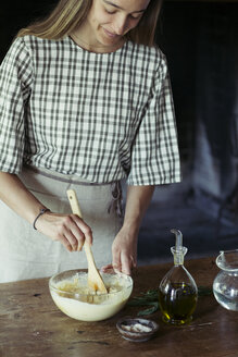 Young woman in kitchen preparing dough for fresh chickpea cake - ALBF00448