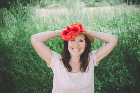 Woman holding a bouquet of red poppies in spring - GEMF02070