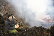 Africa, Democratic Republic of Congo, Virunga National Park, Man sittiing over Nyiragongo volcano crater - REAF00302
