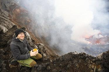 Africa, Democratic Republic of Congo, Virunga National Park, Man sittiing over Nyiragongo volcano crater - REAF00302