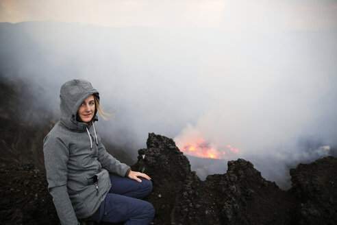 Africa, Democratic Republic of Congo, Virunga National Park, Woman sittiing over Nyiragongo volcano crater - REAF00305