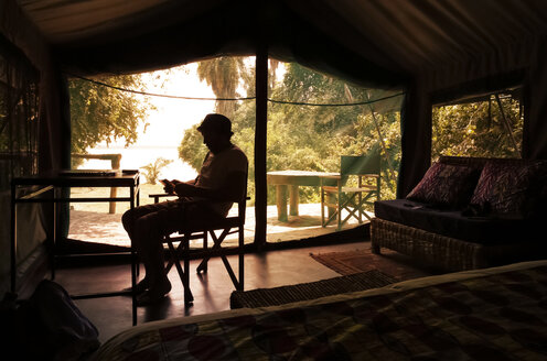 Uganda, Silhouette of a man reading in tent camp - REAF00311