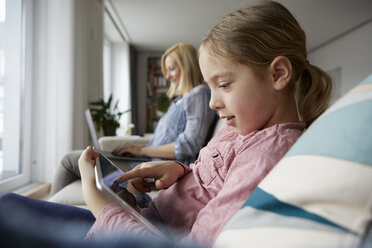 Mother and daughter at home sitting on couch using laptop and tablet - RBF06298