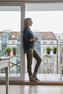 Smiling woman holding cup of coffee looking out of balcony door - RBF06301