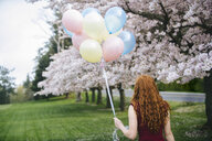 Rear view of young woman with long wavy red hair and bunch of balloons in spring park - ISF09673