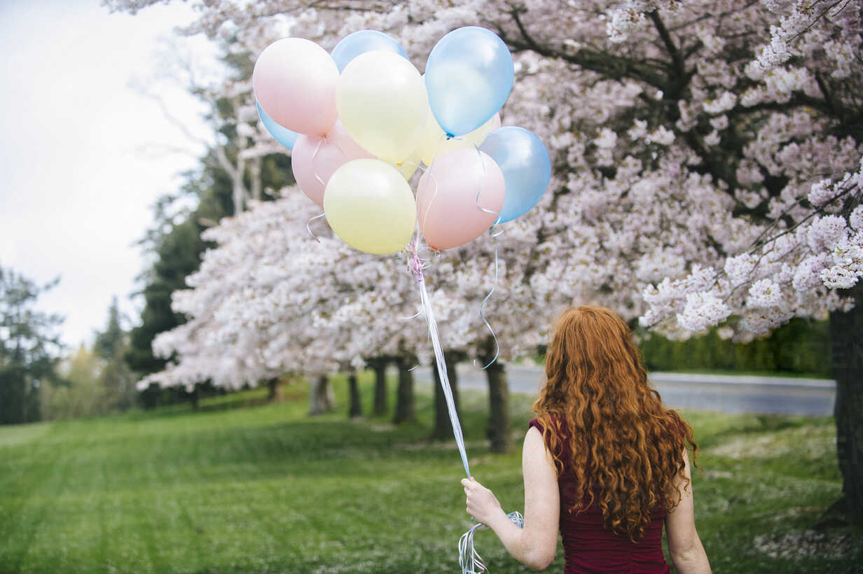 Rear view of young woman with long wavy red hair and bunch of balloons in spring park - ISF09673 - Pete Saloutos/Westend61