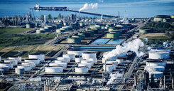 High angle view of white oil storage tanks in coastal oil refinery - ISF09688