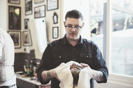 Barber drying clients face with towel in barber shop - CUF31449