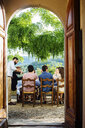 Group of friends, having meal together, outdoors, rear view, photographed through doorway - CUF31494