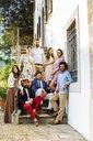 Portrait of group of friends, sitting on villa steps - CUF31497