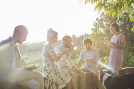 Group of friends relaxing together, sitting on wall, outdoors, eating - CUF31500