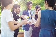 Man pouring champagne for friends, outdoors - CUF31503