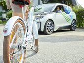 Woman with bicycle in front of electric car - CVF00798