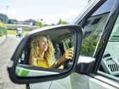 Reflection in wing mirror of smiling woman driving electric car - CVF00801