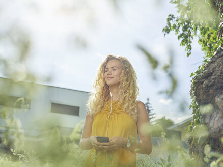 Smiling young woman with cell phone and earphones outdoors - CVF00807