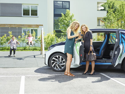 Two women with cell phone at electric car and man and girl in background - CVF00813