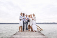 Group of friends standing on pier, holding wine glasses - CUF31615