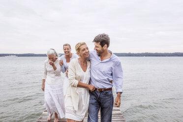 Group of friends walking on pier - CUF31618