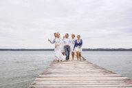 Group of friends walking on pier - CUF31621