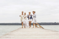 Group of female friends, walking on pier, laughing - CUF31630