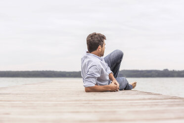 Mature man relaxing on pier, rear view - CUF31633