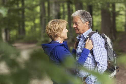 Couple standing face to face in forest - CUF31636