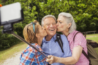 Group of friends taking self portrait, using selfie stick and smartphone, women kissing man on cheek - CUF31645