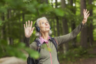 Senior woman in forest, wearing headphones, arms raised - CUF31648