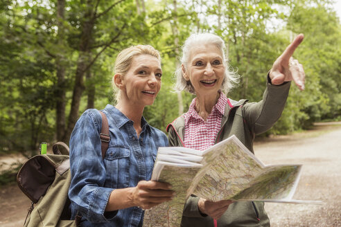 Two female friends on hiking trail, looking at map, pointing - CUF31654