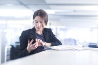 Businesswoman using smartphone in office - CUF31666