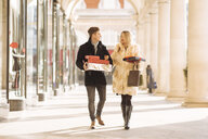 Young couple carrying xmas gifts strolling in Covent Garden, London, UK - CUF31675